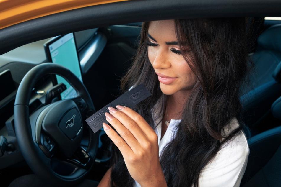 Beim Elektro-Autofahren schnuppert diese Frau am Parfüm, das nach Benzin riechen soll.