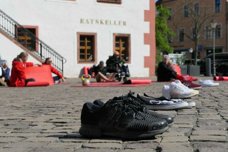 Die Teilnehmer hatten sich dazu auf Yogamatten sitzend auf dem Marktplatz verteilt. Zudem waren Sportschuhe aufgereiht worden.