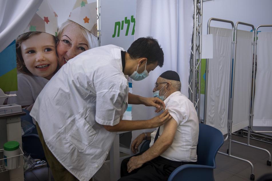 Israel, Tel Aviv: Ein Mann erhält eine dritte Dosis des Corona-Impfstoffes von Biontech/Pfizer von einem medizinischen Mitarbeiter in einem Impfzentrum.