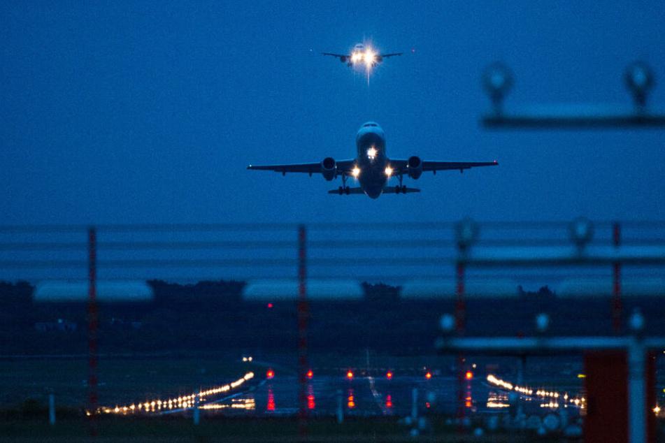 Ein Flugzeug startet in der Dunkelheit am Hamburger Flughafen, während ein anderes im Landeanflug ist.