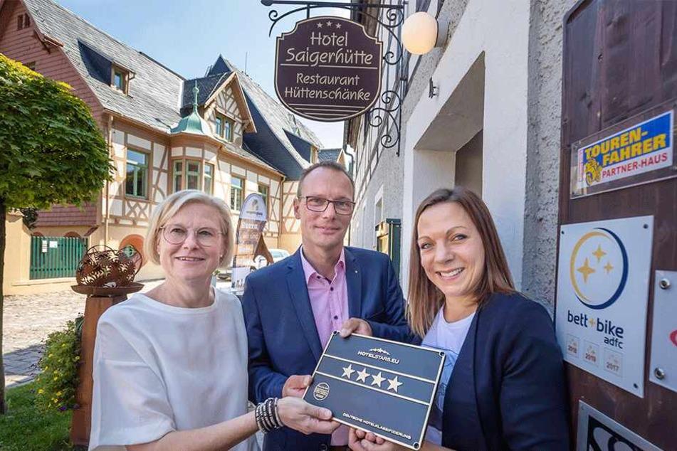 DEHOGA-Geschäftsführerin Franziska Luthardt (37) übergibt die Vier-Sterne-Plakette an die Hotel-Inhaber Brit (51) und Markus Gorny (50).