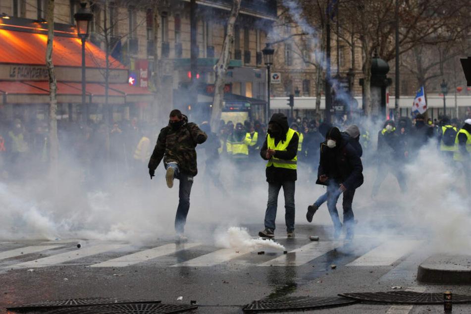 "Demonstranten der ""Gelben Westen"" treten gegen Tränengasgranaten."