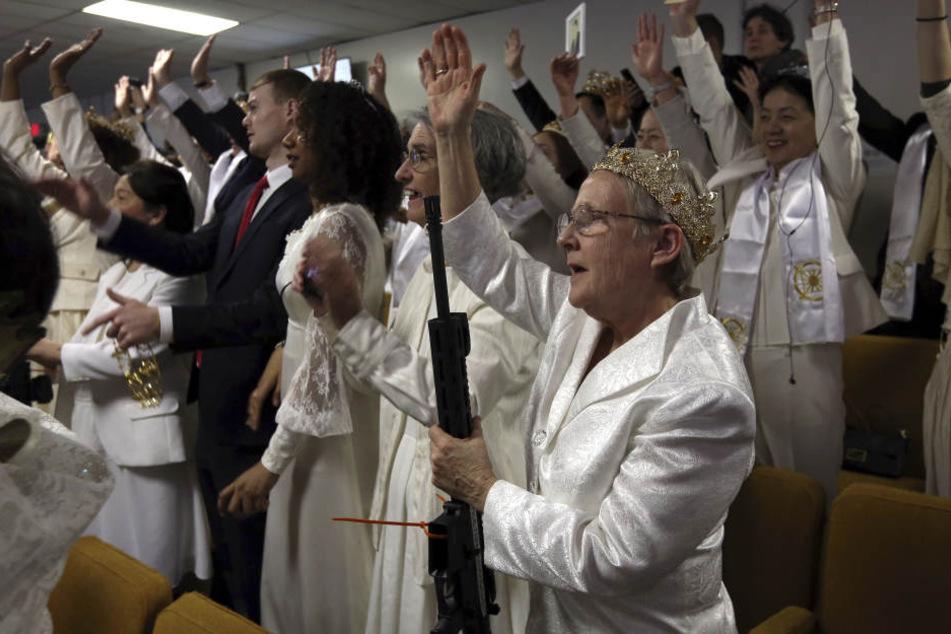 Eine Frau trägt eine Krone und hält jubelnd ein AR-15 Gewehr bei einem Gottesdienst in der Kirche World Peace and Unification Sanctuary.