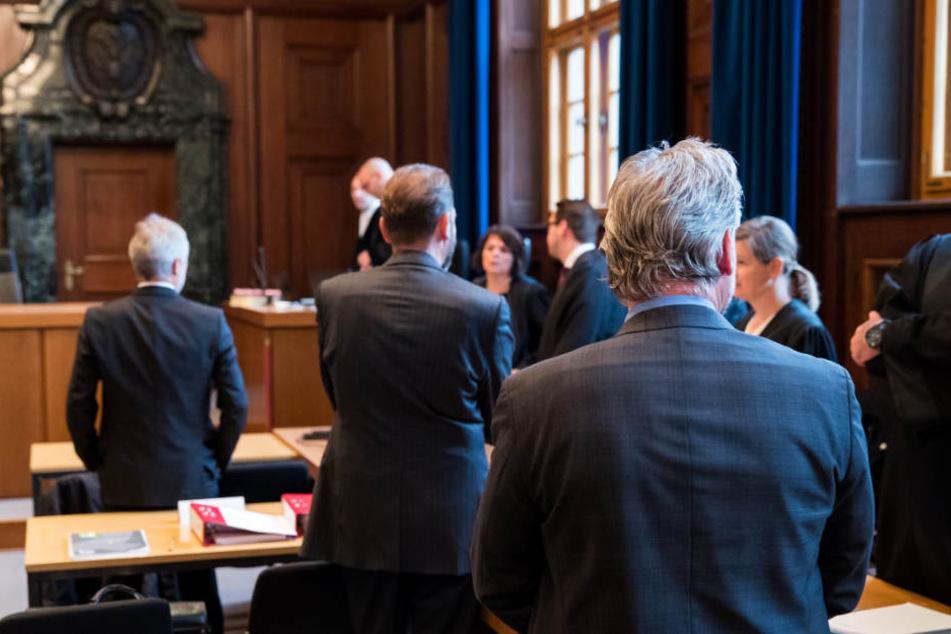 Drei von sechs angeklagten Beamten im Sitzungssaal des Landgerichts Nürnberg-Fürth.