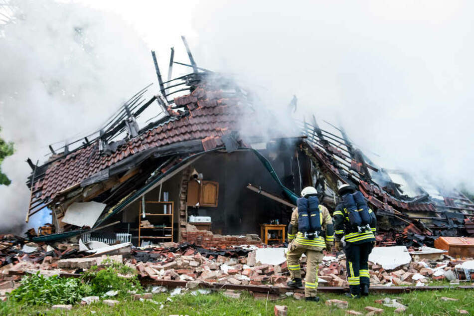 Feuerwehrleute stehen vor den Trümmern des Hauses in Wohltorf.