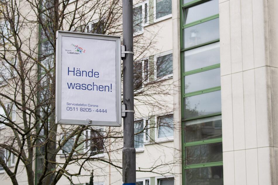 """Ein Schild mit der Aufschrift """"Hände waschen!"""" als Aufruf der Stadt Laatzen in der Region Hannover hängt an einer Straßenlaterne."""