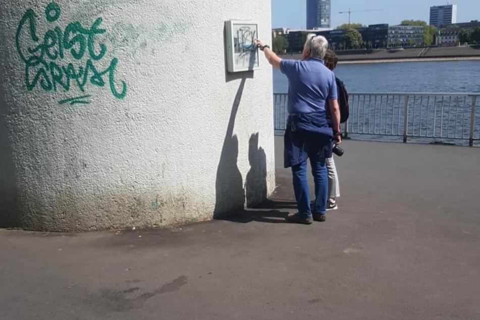 Touristen versuchen die Tafel am Pegel Köln zu lesen.