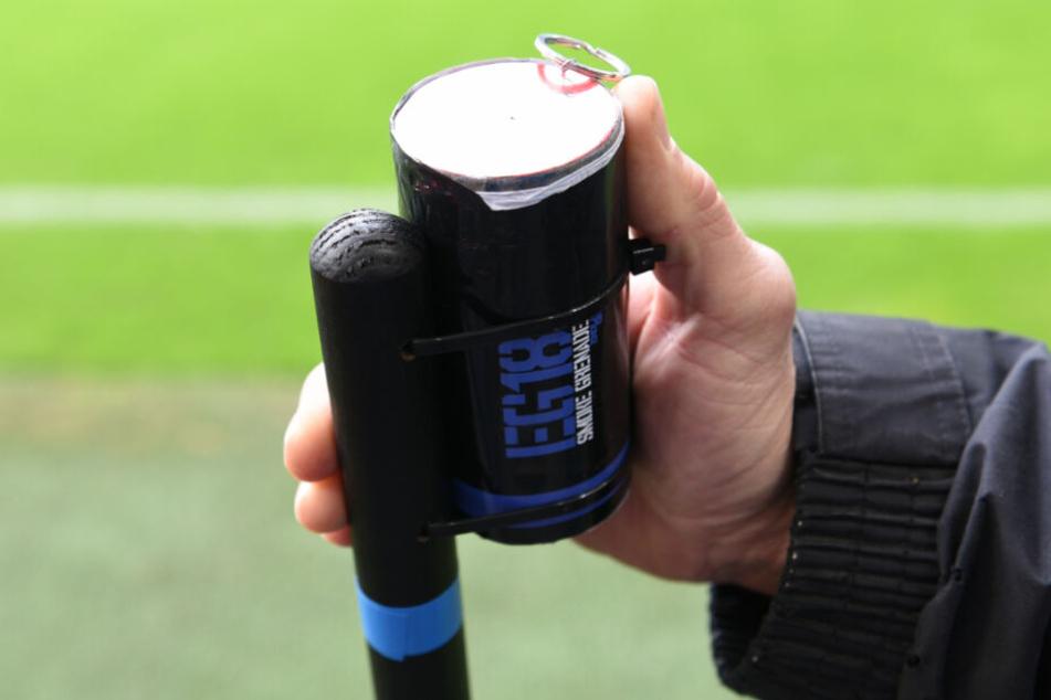 Ein Fan hält eine Rauchgranate in der Hand.
