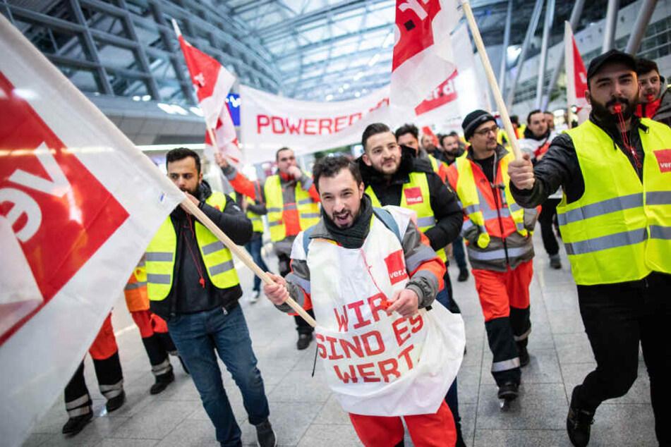 Gewerkschaftler von Verdi demonstrieren mit einem Plakat und Fahnen im Gebäude des Düsseldorfer Flughafens.
