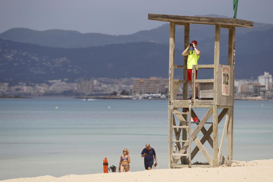 :Ein Rettungsschwimmer beobachtet den Strand von Arenal. Am Ballermann nehmen die Rettungsschwimmer am Samstag ihre Arbeit wieder auf. (Zu dpa «Vorsichtiger Start der Badesaison am Ballermann»)