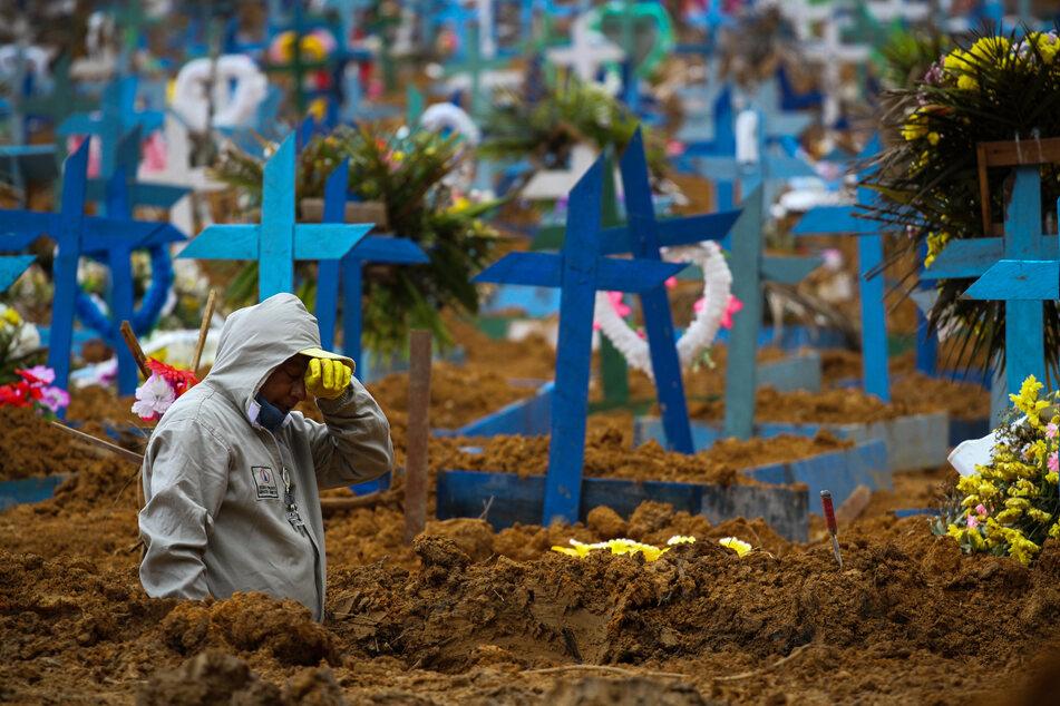 Brasilien, Manaus: Ein Mann in Schutzanzug ist während seiner Arbeit auf dem Friedhof Nossa Senhora Aparecida erschöpft. Nach Asien, Europa und den USA hat die Corona-Pandemie Lateinamerika mit voller Kraft erwischt. (Archivbild)