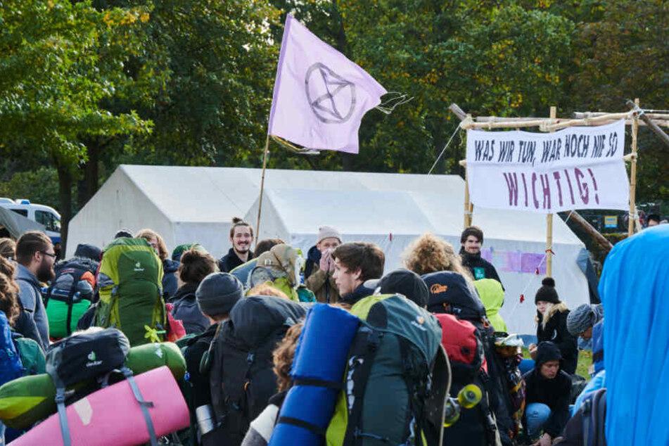 """Teilnehmer kommen auf der Wiese vor dem Reichstag ins sogenannte """"Klimacamp""""."""