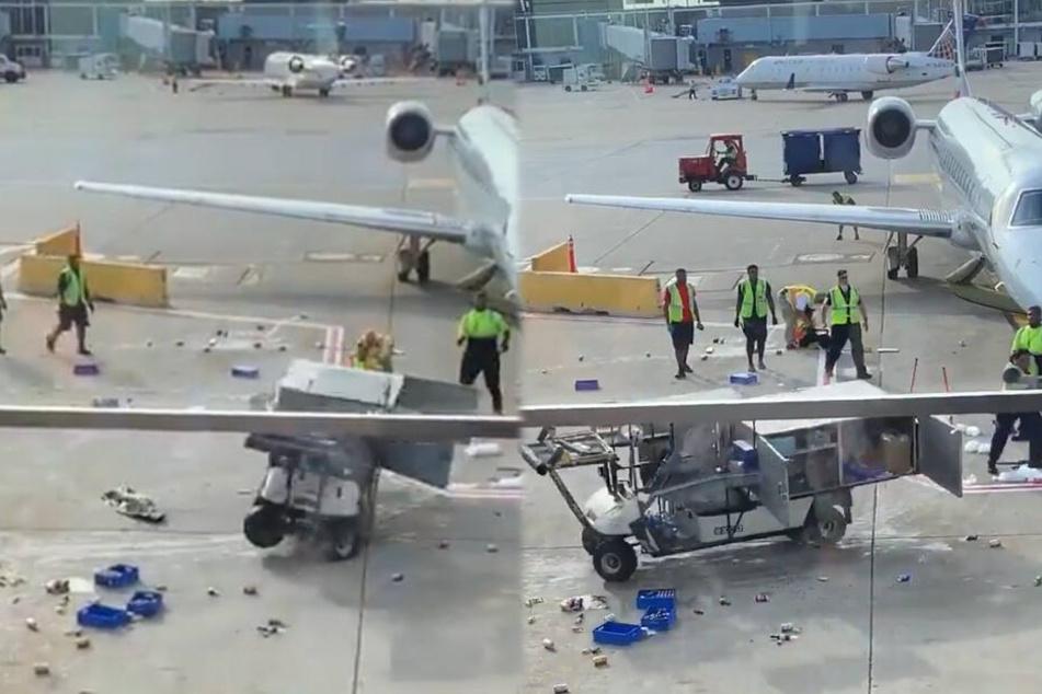Hilflose Mitarbeiter stehen um das Flughafenfahrzeug, einige retten sich mit einem Sprint zu Seite.