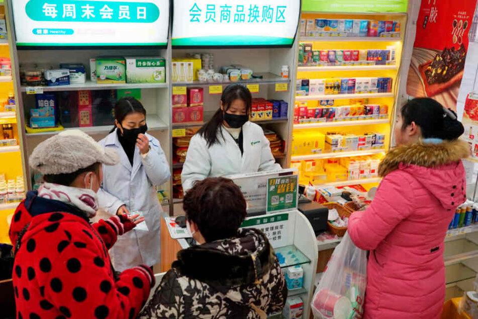 Mitarbeiterinnen verkaufen in einer Apotheke Atemschutzmasken.