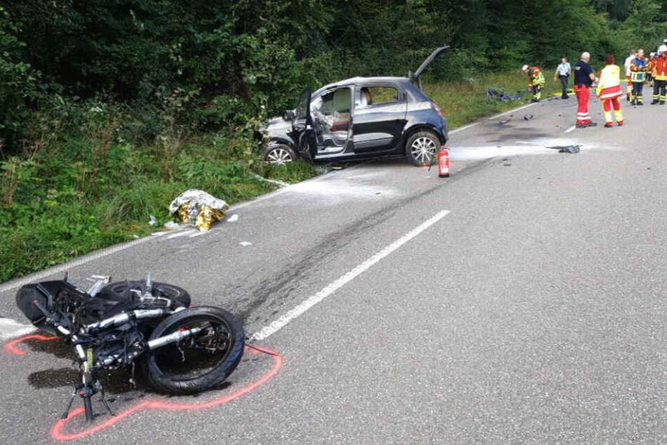 Das Motorrad liegt auf der Straße, im Hintergrund das Auto.