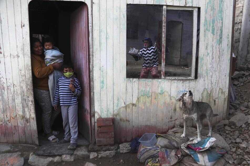 """Jhona Zapata, dessen Clownsname """"Jijolin"""" lautet, spiegelt sich im Fenster eines Hauses wider, als er in einem Armenviertel am Stadtrand von Lima karamellisierte Äpfel zum Verkauf anbietet."""