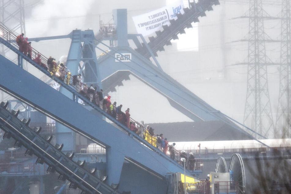 Die Polizei (r.) holt die Aktivisten einzeln vom Bagger herunter. Das Kraftwerk im Ruhrgebiet soll entgegen der Empfehlung der Kohlekommission im Sommer dieses Jahres ans Netz gehen.