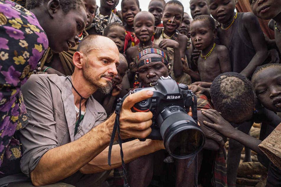 Markus Mauthe (vorne, Zweiter von links) schoss Fotos an den entlegensten Orten der Erde - und führte sie den verschiedenen Stämmen vor.