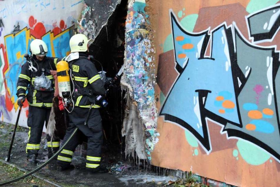 Einsatzkräfte der Feuerwehr löschen die restlichen Glutnester hinter der Fassade.