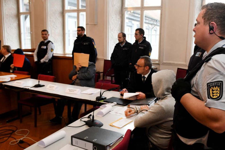 Der Angeklagte Vater (Mitte) wird mit seinen Söhnen beim Prozessauftakt von Justizwachtmeistern bewacht.