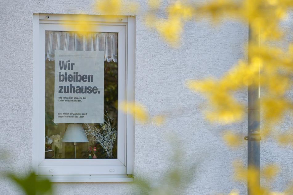 """""""Wir bleiben zuhause. Und wir danken allen, die den Laden am Laufen halten."""" steht auf einer Zeitungsseite, die in einem Fenster im Landkreis Leipzig hängt."""