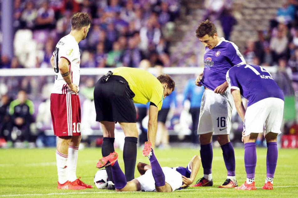 Schiedsrichter Sören Storks kümmert sich um den verletzten Philipp Riese, der nach einem Zusammenprall mit Almog Cohen (Ingolstadt) am Boden liegen blieb.