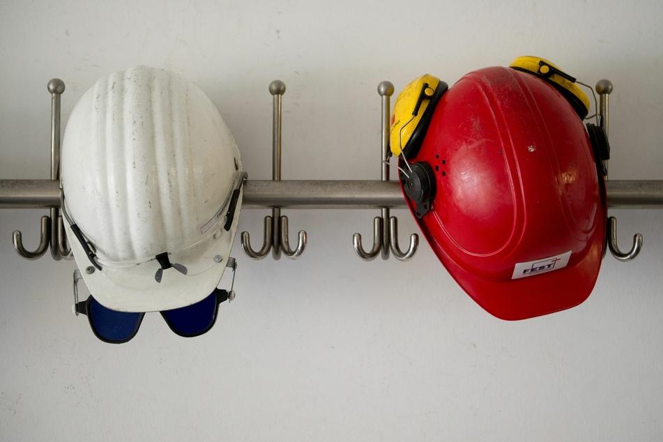 Schutzhelme hängen an Haken. Auch das Baugewerbe wurde von der Rezession getroffen.