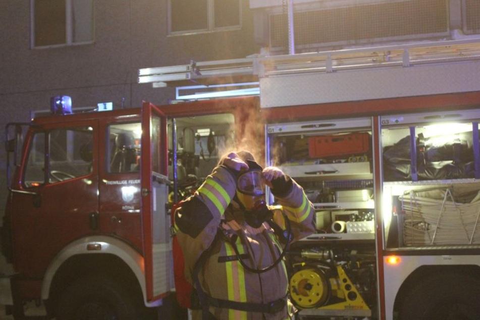 Ein Kamerad der Feuerwehr kommt qualmend aus der Brandwohnung. Zum Zeitpunkt des Feuers war darin glücklicherweise keine Person.