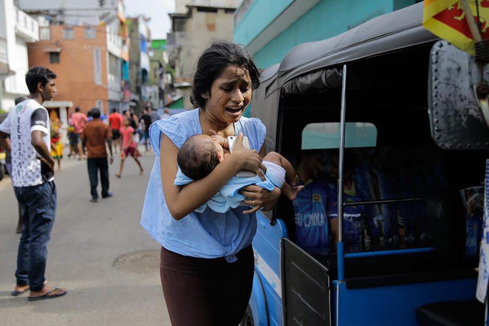 Herzergreifend! Eine sri-lankische Frau, die in der Nähe des St-Antonius-Kirche wohnt, läuft mit ihrem Kind in Sicherheit.
