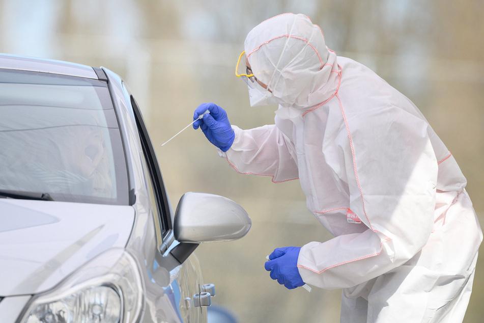 Ein Mitarbeiter führt in einem Corona-Abstrichzentrum einen Test auf das Coronavirus Sars-Cov-2 durch.