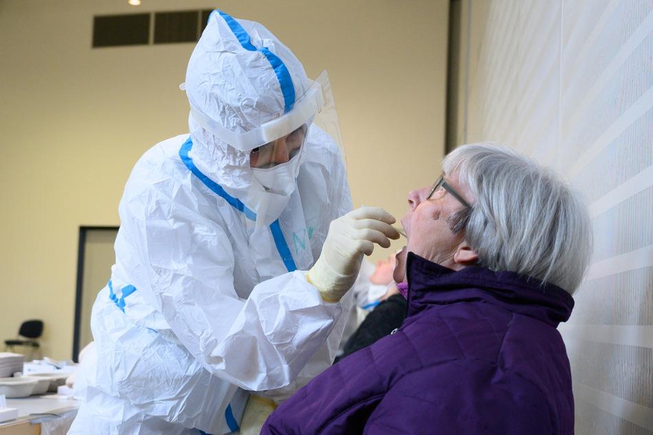 Eine Seniorin sitzt während eines Corona-Massentests in der Veranstaltungshalle vor einer Mitarbeiterin vom Gesundheitsamt. Wegen hohen Infektionszahlen sollen am Mittwoch Massentests im Wartburgkreis starten.