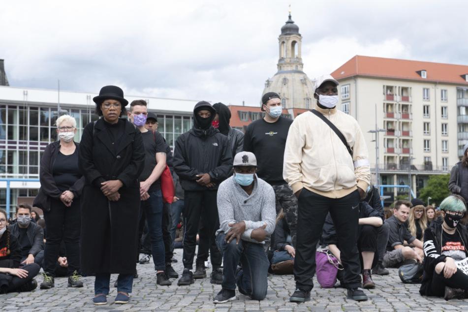 """Teilnehmer stehen, knien und sitzen während einer """"Silent Demo"""" zur Erinnerung an den gewaltsamen Tod von George Floyd auf dem Dresdner Altmarkt."""