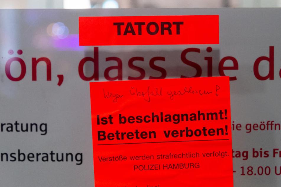 An der Tür der Bankfiliale klebt ein großer Zettel, der auf den Tatort hinweist.