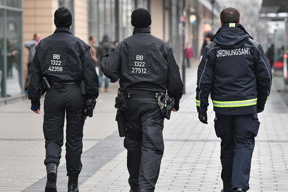 Ein Mitarbeiter des Ordnungsamtes und zwei Beamte der Bereitschaftspolizei gehen auf Streife vor dem Einkaufszentrum Blechen-Carré