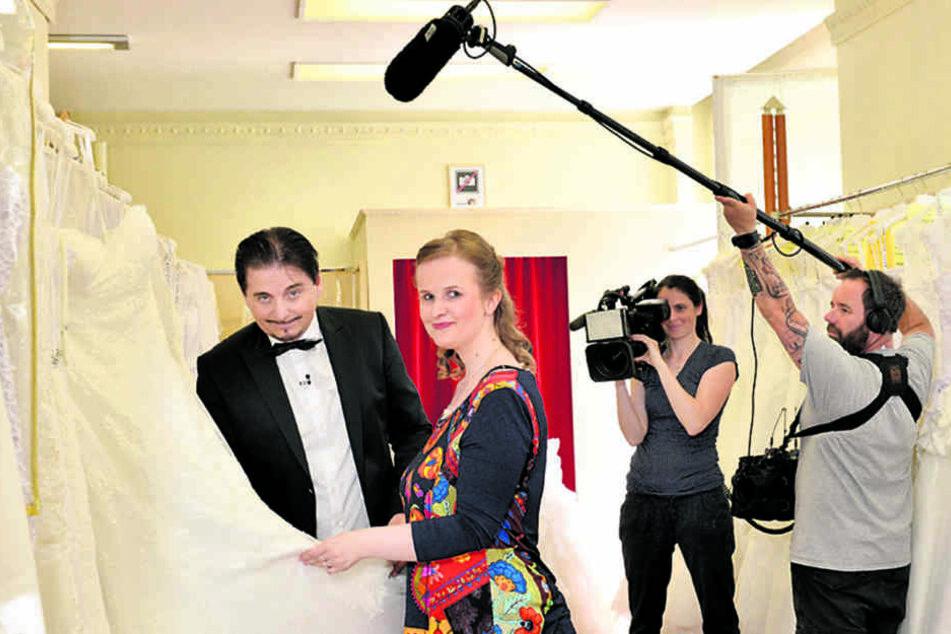 """Braut Anne (26) sucht vor laufender VOX-Kamera ein Brautkleid aus.  Mittlerweile hat Uwe Herrmann (54) schon 140 Folgen von """"Zwischen Tüll &  Tränen"""" gedreht."""