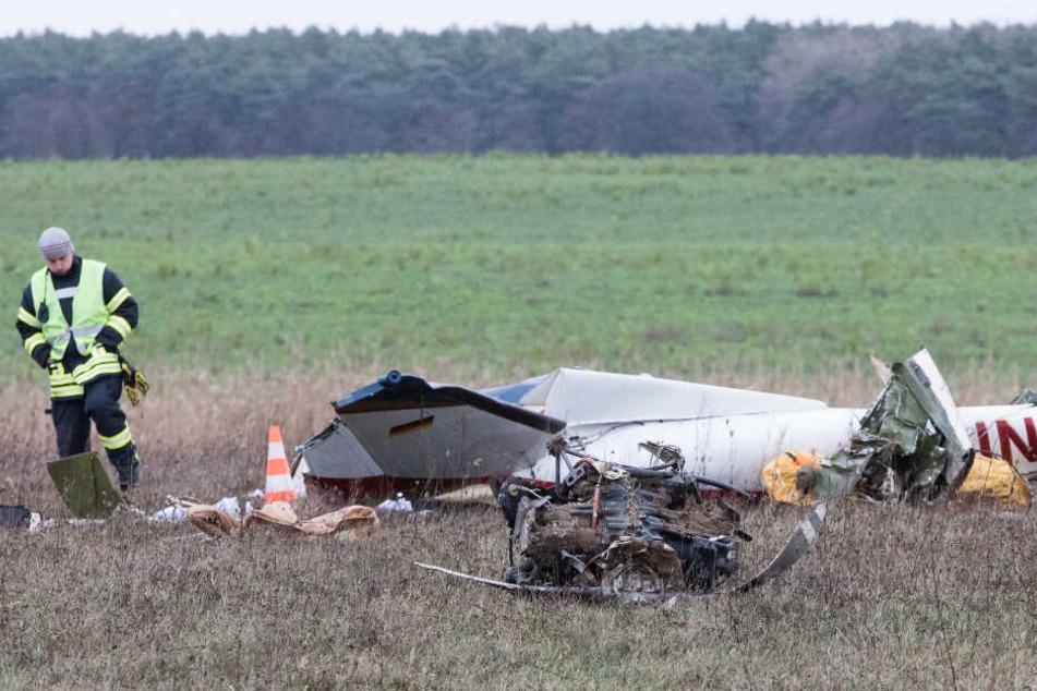 Die Trümmer eines Flugzeugs liegen nach einem Absturz auf einem Feld.
