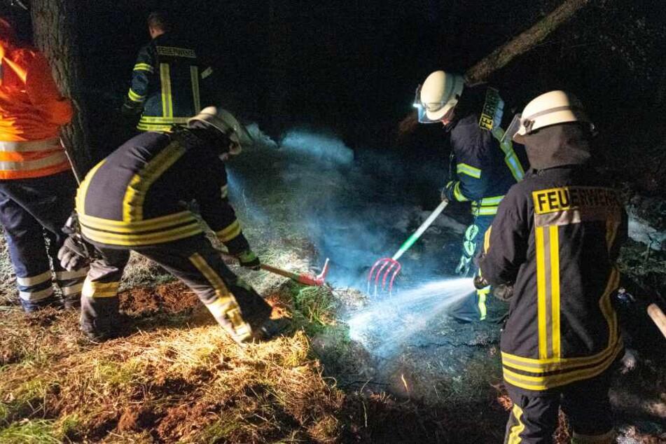 Feuerwehrleute legen Gräben im Moor an.