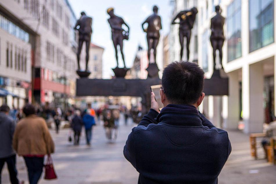 """Ein Tourist fotografiert die """"Unzeitgemäßen Zeitgenossen"""" in der Grimmaischen Straße in Leipzig."""