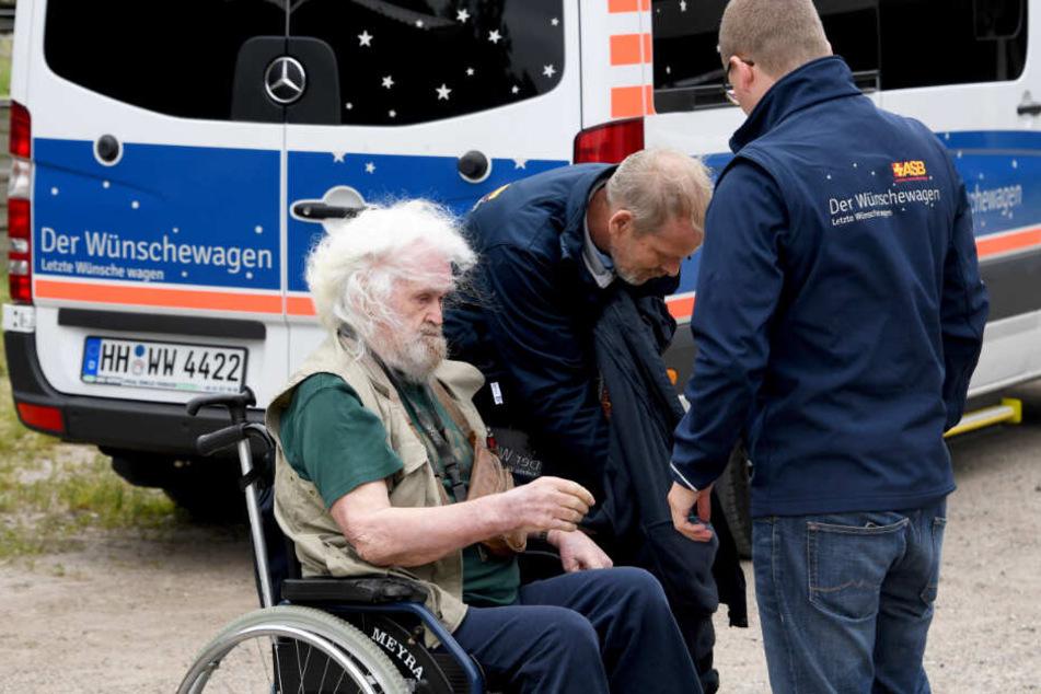 Helfer des ASB bringen Edzard Riek mit dem Wünschewagen zum Pferdehof.
