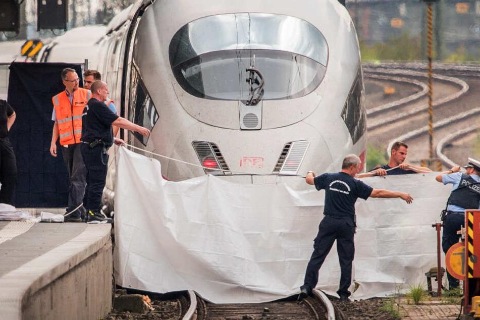 Polizisten und Feuerwehrleute spannen im Hauptbahnhof eine weiße Plane als Sichtschutz vor einen ICE.