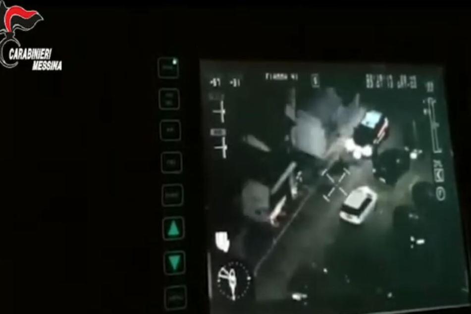 Aufnahmen einer Nachtbildkamera zeigen den Polizeieinsatz auf der italienischen Mittelmeerinsel Sizilien (Standbild aus einem Video).