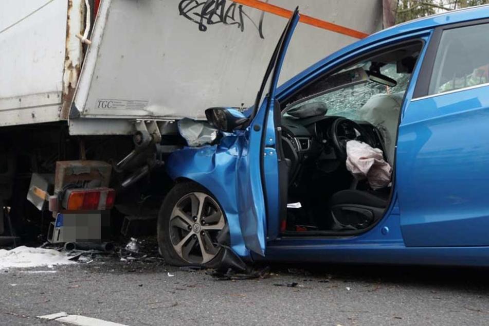 Das Auto steckt mit der kompletten Front unter dem Laster.