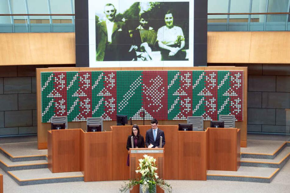 Die Enkel des Zeitzeugen und Auschwitz-Überlebenden Gary Wolff, Danielle Wolff (l) und Julian Wolff (r) stehen im Plenarsaal des Landtages am Rednerpult und erzählen die Geschichte ihres Opas.