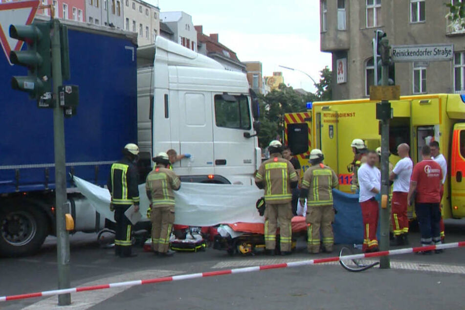 Rettungskräfte decken den Verletzten mit einer Plane ab.