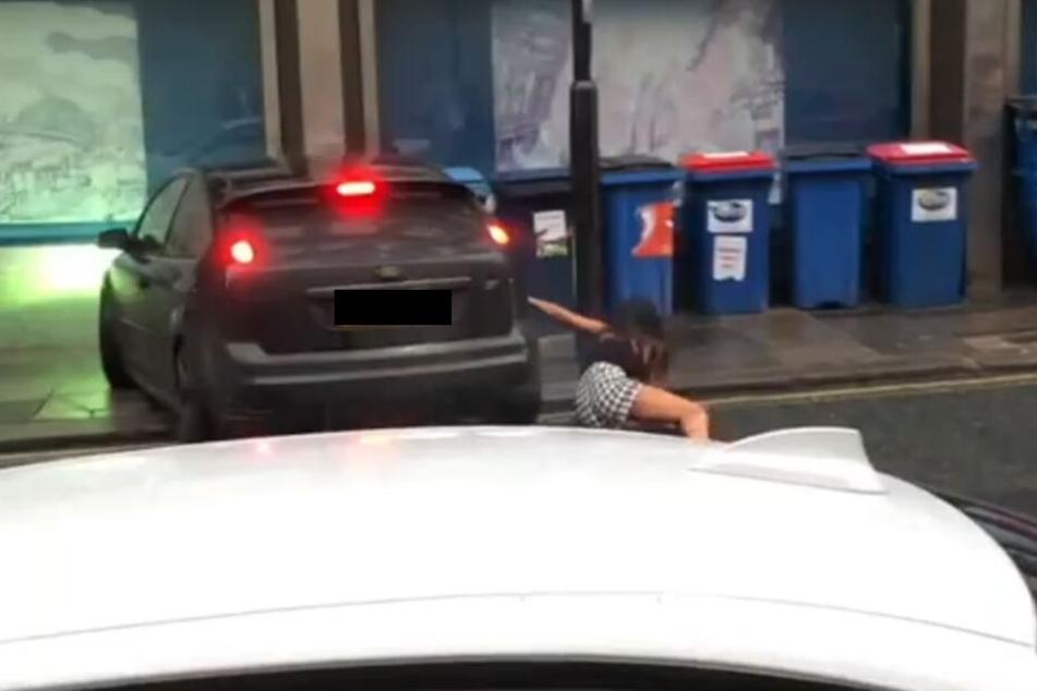 Der Fahrer versucht die Frau scheinbar umzufahren. Dabei stürzt die Frau.