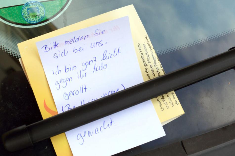 """Ein Zettel mit der Aufschrift: """"Bitte melden Sie sich bei uns. Ich bin ganz leicht gegen ihr Auto gerollt"""", klemmt an einem PKW hinter einem Scheibenwischer."""
