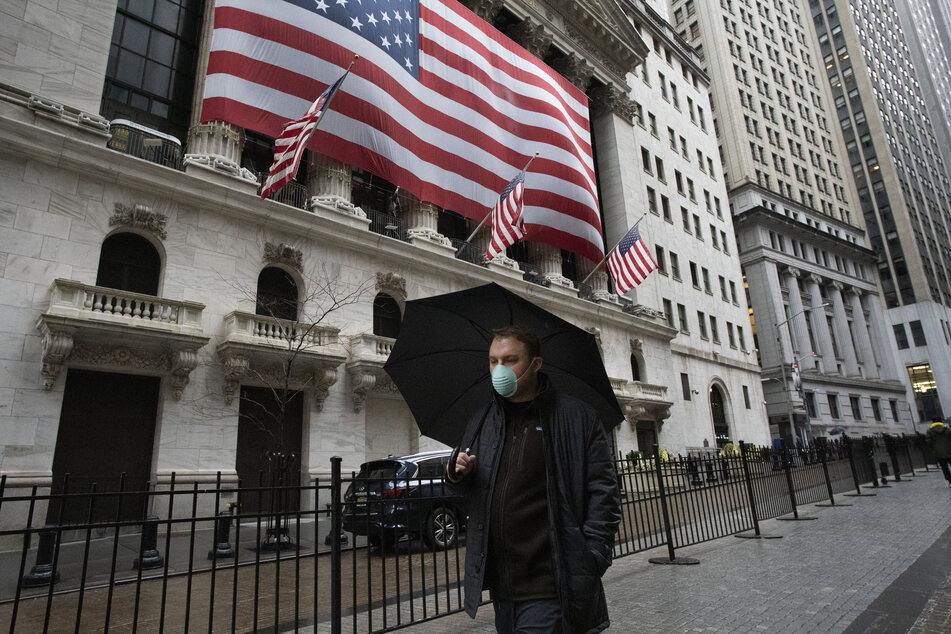 Ein Mann mit Regenschirm und einer Mundschutzmaske geht an der New Yorker Börse vorbei.