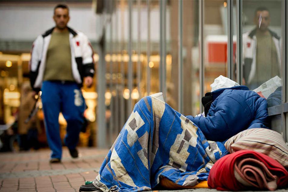 Armut gibt es auch in Deutschland: Ein Obdachloser schläft in einer Fußgängerzone in Dortmund auf dem Boden - eingepackt in Decken und zwischen Plastiktüten.