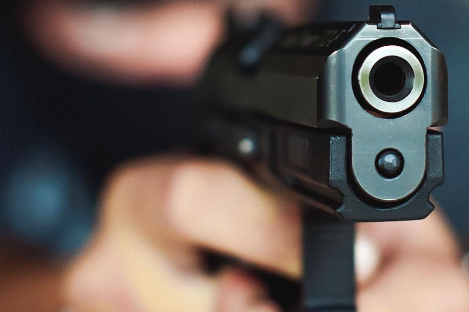 Der Räuber hatte eine Schusswaffe dabei und drohte damit (Symbolbild).
