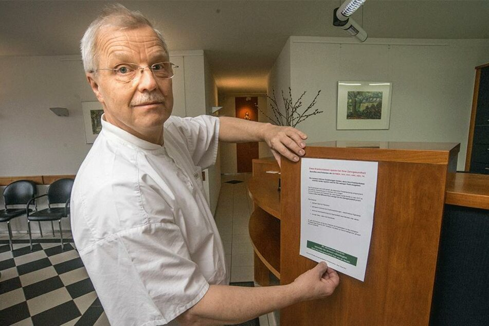 """Zahnarzt Dr. Holger Weißig (60), Vorstandsvorsitzender der Kassenzahnärztlichen Vereinigung Sachsen, hängt ein """"Flugblatt"""" in seiner Praxis aus."""